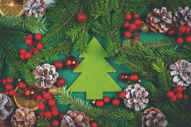 Decoración navideña con conos y ramas de pino en verde