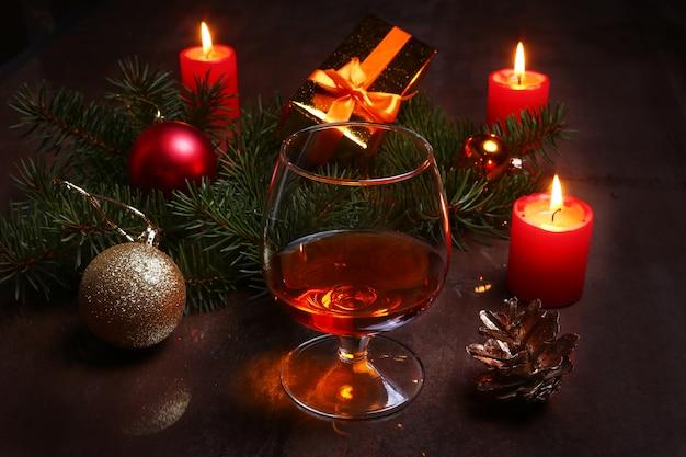Decoración navideña con copa de coñac o whisky, velas rojas, caja de regalo y árbol de navidad.