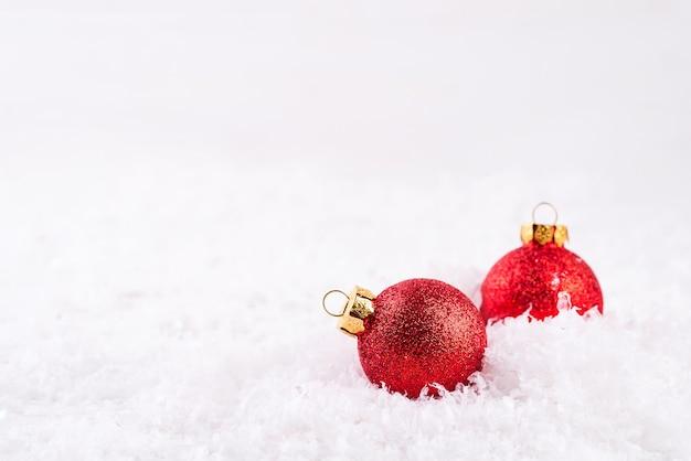 Decoración navideña con dos bolas rojas en la nieve.