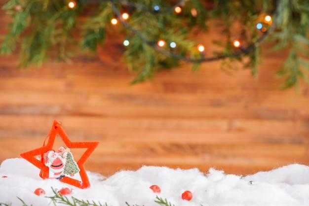 Decoración navideña estrella en nieve con guirnalda.