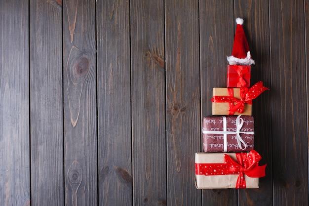 Decoración navideña y lugar para texto. árbol de año nuevo hecho de regalos se encuentra en una mesa de madera