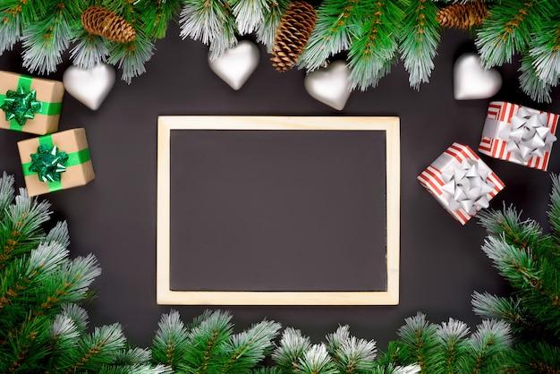 Decoración navideña con ramas de abeto sobre un fondo oscuro con espacio de copia