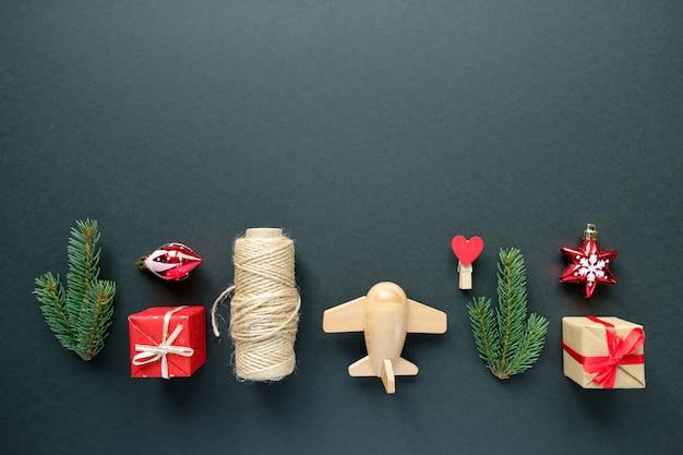 Decoración navideña con ramas, estrellas y cajas de regalo sobre fondo negro