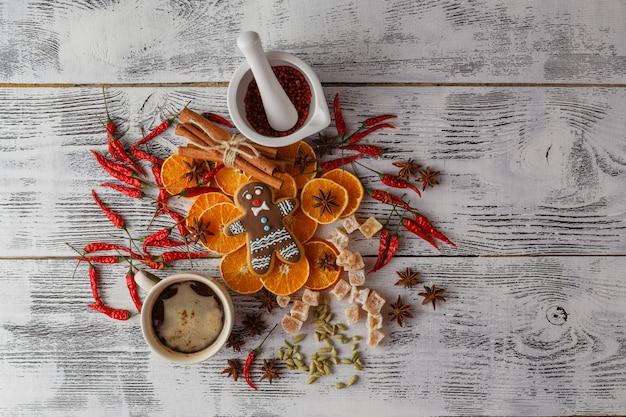 Decoración navideña sobre fondo de madera con canela, naranja, nueces