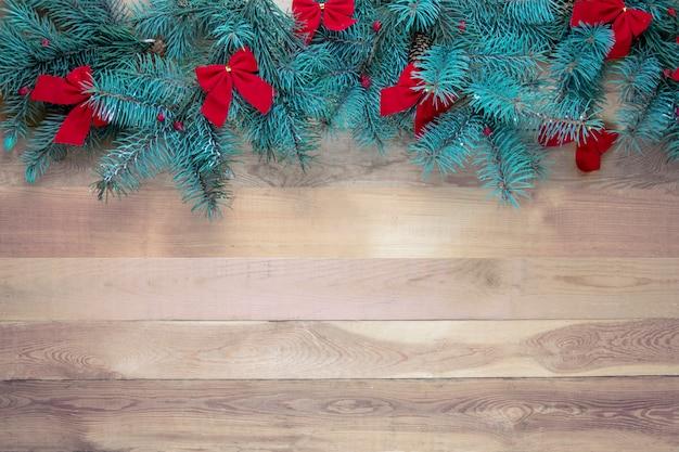 Decoración navideña sobre un fondo de madera vintage con lazos rojos