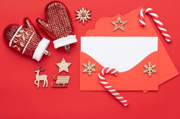Decoración navideña sobre un fondo rojo y que consta de un sobre rojo con un membrete blanco vacío en el interior para el texto y decorado con dulces navideños