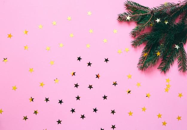 Decoración navideña sobre un fondo rosa con estrellas doradas