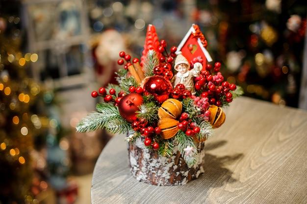 Decoración navideña de tocón decorada con bayas, bolas de cristal, cáscara de naranja seca y juguetes.
