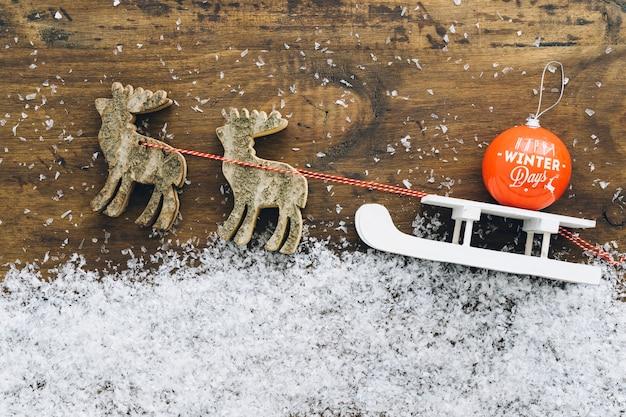Decoración de nieve de navidad con bola en trineo