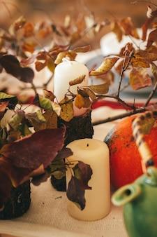 Decoración de otoño con calabaza, velas y vajilla.