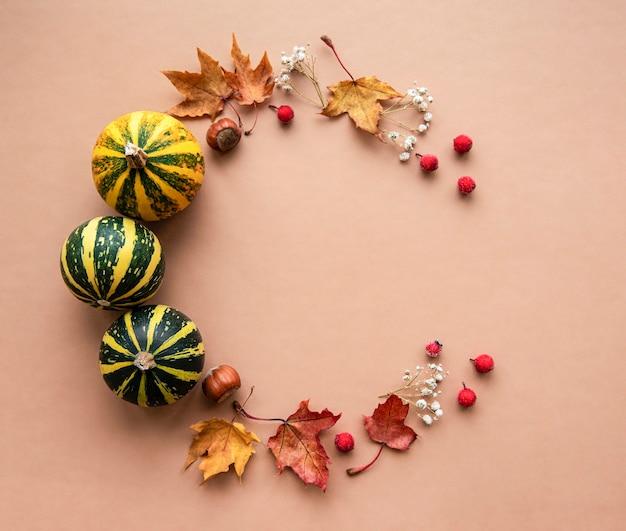Decoración de otoño con calabazas y hojas de arce secas en forma de círculo sobre un fondo marrón