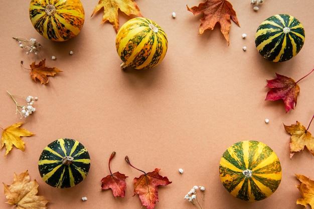 Decoración de otoño con calabazas y hojas de arce secas sobre un fondo marrón