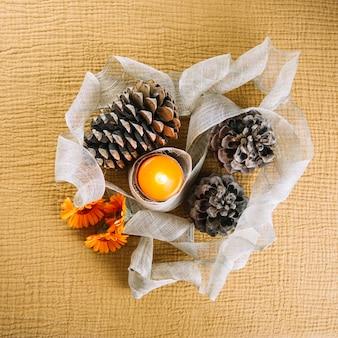 Decoración de otoño con vela y conos de pino