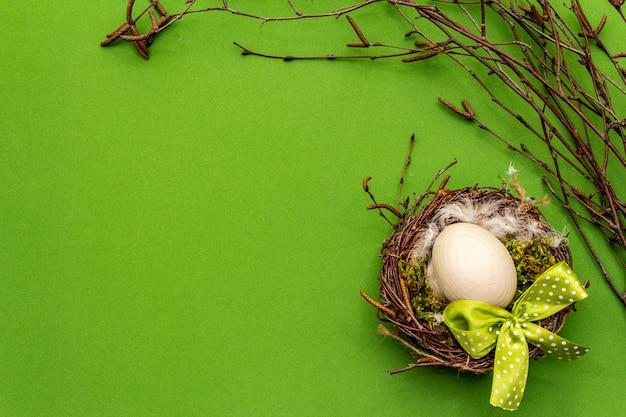 Decoración de pascua cero residuos, concepto de bricolaje. elemento de diseño y decoración. nido de pájaro, huevo, musgo, ramas de abedul, pluma. fondo verde