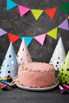 Decoración con pastel rosa y sombreros de fiesta
