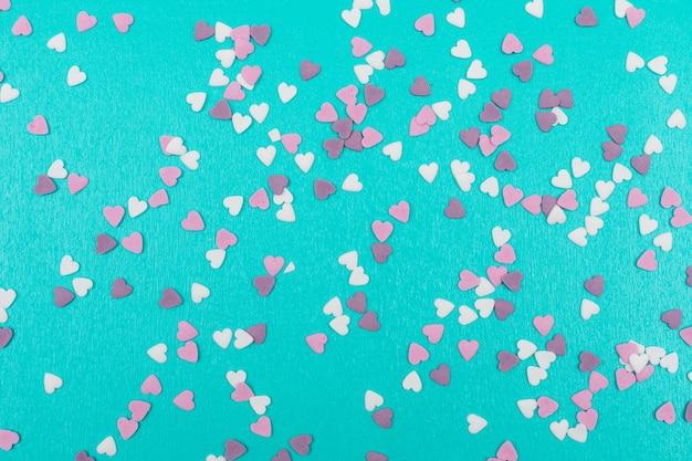 Decoración de pequeñas galletas en forma de corazón sobre superficie azul