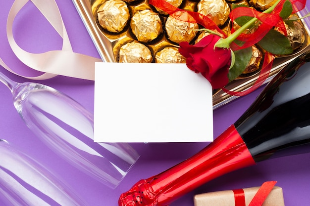 Decoración plana con caja de chocolate y botella de vino.