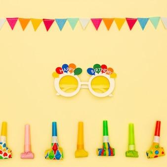 Decoración plana con gafas de fiesta y sopladores.