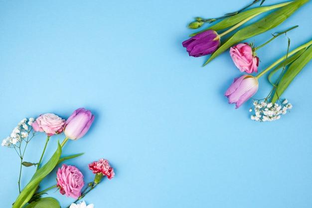 Decoración realizada con variedad de flores sobre fondo azul.