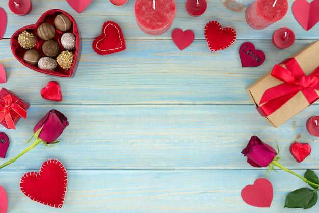 Decoración romántica del día de tarjetas del día de san valentín con las rosas y el chocolate en una tabla de madera azul.