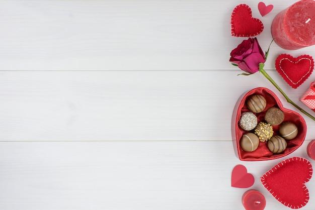 Decoración romántica del día de tarjetas del día de san valentín con las rosas y el chocolate en una tabla de madera blanca.