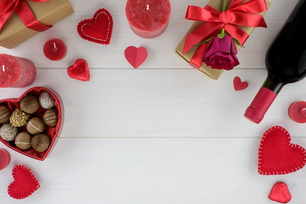 Decoración romántica del día de tarjetas del día de san valentín con las rosas, el vino y el chocolate en una tabla de madera blanca.