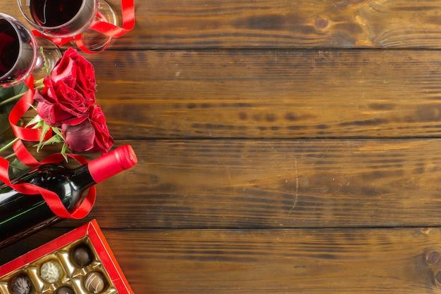 Decoración romántica con rosas, vino y chocolate del día de san valentín en una mesa de madera marrón