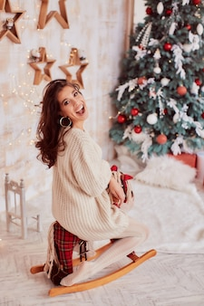 Decoración de vacaciones de invierno. colores cálidos. encantadora mujer morena en suéter beige