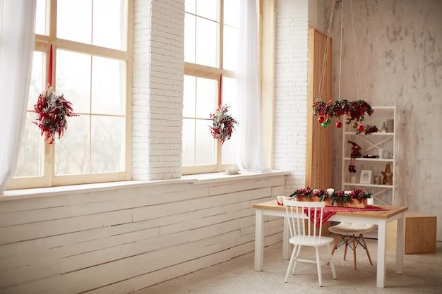 Decoración de vacaciones de invierno. preparaciones de estudio. guirnaldas hechas de frutos rojos y arbol de navidad.