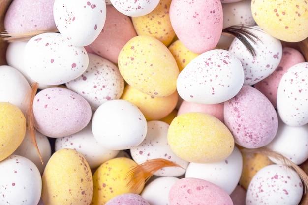 Decoración de vacaciones de semana santa. fondo decorativo colorido divertido de los huevos de pascua del chocolate. de cerca. vista superior. huevos rosados amarillos blancos para el convite de pascua.