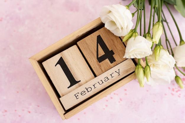 Decoración de la vista superior con mensaje del 14 de febrero y flores.