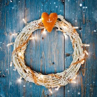 Decoraciones de año nuevo alrededor del espacio vacío de la carta de navidad para guirnaldas de luces ardientes de texto sobre fondo de madera azul.