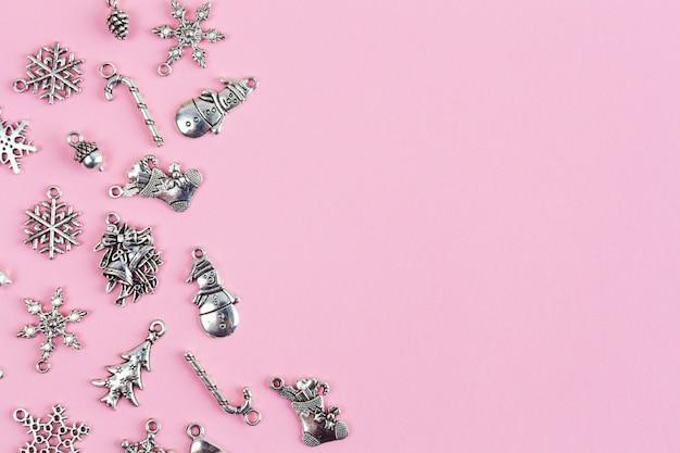 Decoraciones para árboles de navidad dispuestas sobre fondo rosa con espacio de texto - primer plano