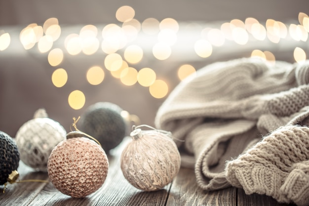 Decoraciones para árboles de navidad sobre luces de navidad bokeh en casa sobre mesa de madera con suéter en una pared y decoraciones.