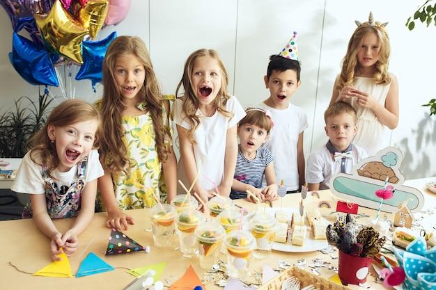 Decoraciones de cumpleaños de niña. mesa con pasteles, bebidas y artículos de fiesta.