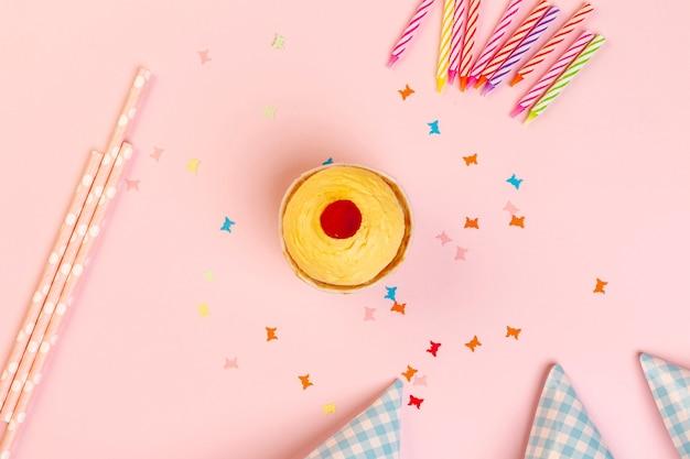 Decoraciones de cupcake y cumpleaños sobre un fondo rosa