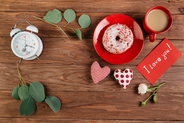 Decoraciones del día de san valentín cerca del desayuno con donut.