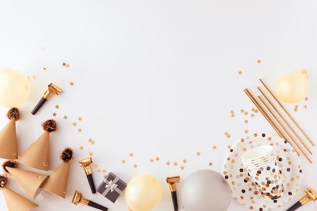 Decoraciones doradas y negras para la fiesta en el fondo de color blanco.