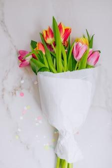 Decoraciones de estrellas doradas, confeti vibrante y tulipanes rosados y rojos sobre fondo de mármol
