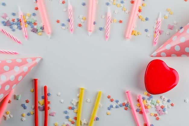 Decoraciones de fiesta con chispas de azúcar, caja de regalo sobre una mesa blanca