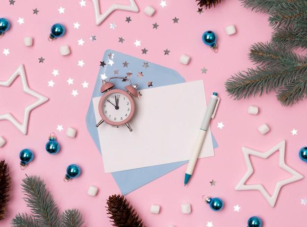 Decoraciones de invierno de navidad, sobre con despertador, copos de nieve y tarjeta de felicitación en blanco sobre fondo rosa