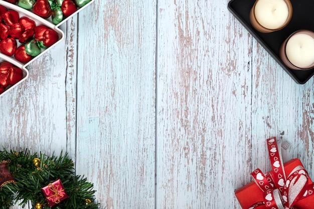 Decoraciones para la mesa de la cena de navidad con caramelos de chocolate, velas aromáticas y una caja de regalo roja.