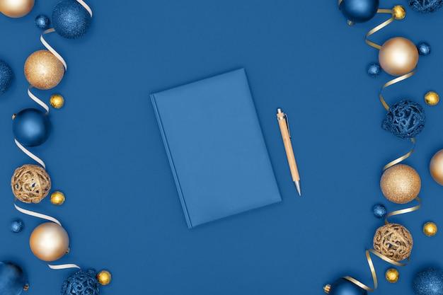 Decoraciones de navidad y año nuevo y cuaderno y pluma sobre fondo de papel azul. lista de deseos o concepto de objetivos. vista superior, plano, copia espacio. color de moda del año 2020.