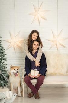 Decoraciones de navidad. joven pareja feliz caricias y besos mientras está sentado en un banco junto a un perro