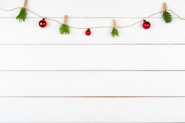 Decoraciones de navidad sobre fondo blanco de madera con espacio de copia