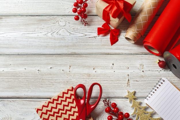 Decoraciones navideñas y artículos de envoltura de regalos sobre fondo de madera, espacio de copia