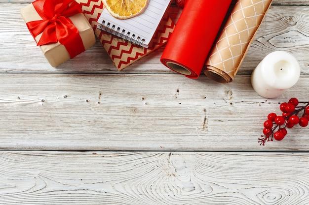 Decoraciones navideñas y artículos de envoltura de regalos sobre fondo de madera