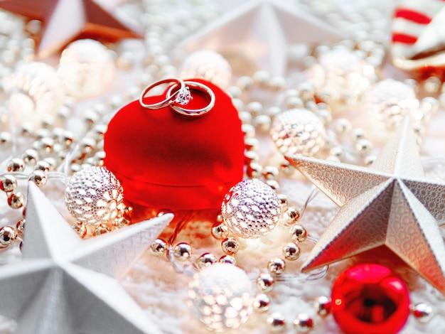 Decoraciones navideñas y caja de regalo de corazón rojo con anillos de diamantes de boda