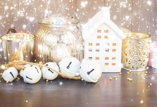 Decoraciones navideñas y casa blanca de invierno con luces brillantes y nieve.