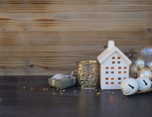 Decoraciones navideñas y casa de invierno blanca con luces brillantes y caja de regalo, espacio de copia